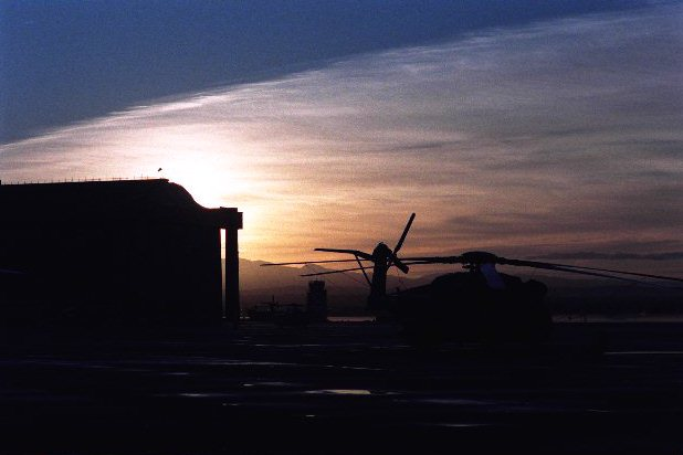 California sunset silouet of the blimp hanger and a Super Stallion